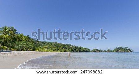 PUNTA LEONA, COSTA RICA - SEPTEMBER 7, 2008: People at the beach in Punta Leona, Costa Rica. This pristine white sand beach is surrounded by lush primary and secondary forests. - stock photo