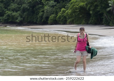 PUNTA LEONA, COSTA RICA - SEPTEMBER 6, 2008: Young woman at the beach in Punta Leona, Costa Rica. This pristine white sand beach is surrounded by lush primary and secondary forests. - stock photo