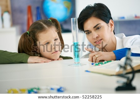 Pupil and teacher looking at test tube in chemisty class at elementary school. Teacher explaining. - stock photo