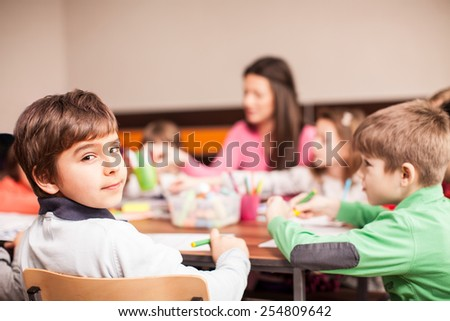 Pupil boy sitting together with his friends, boys and girls around the table in classroom and drawing. With them is their young and beautiful teacher. Boy looking at camera and smiling.  - stock photo