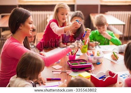 Pupil boys and girls sitting together around the table in classroom and drawing.  - stock photo