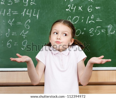 Pupil doesn't know the right answer and spreads her arms - stock photo