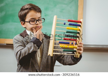 Pupil dressed up as teacher holding abacus in a classroom - stock photo