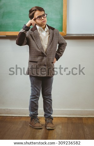 Pupil dressed up as teacher thinking in front of chalkboard in a classroom - stock photo