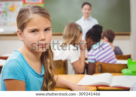 Pupil frowning at camera during class at the elementary school