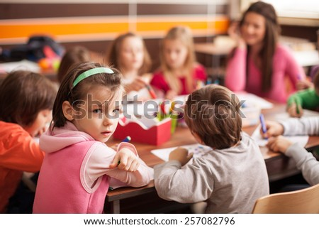 Pupil girl sitting together with her friends, boys and girls around the table in classroom and drawing. With them is their young and beautiful teacher. Girl looking at camera. - stock photo