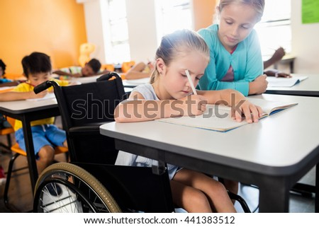 Pupil helping another at desk in classroom - stock photo