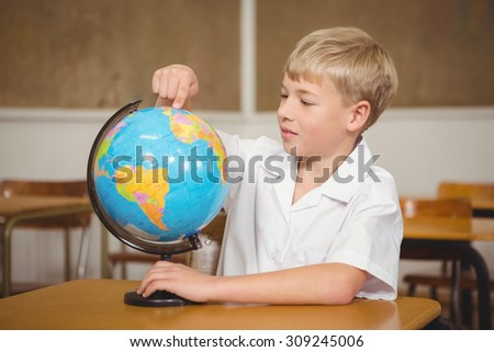Pupil pointing to a place on a globe at the elementary school - stock photo