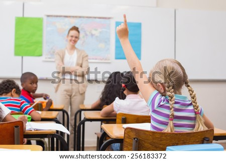 Pupil raising hand during geography lesson in classroom at the elementary school