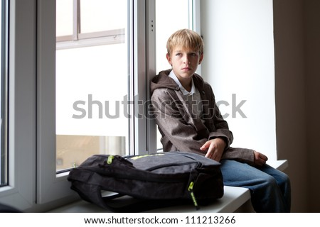 Pupil sits at a window outdoor - stock photo