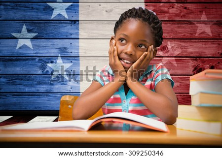 Pupil sitting at her desk against composite image of usa national flag - stock photo