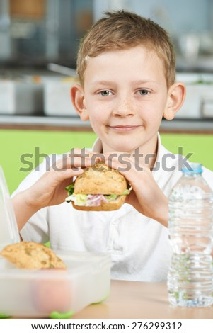 Pupil Sitting In School Cafeteria Eating Healthy Packed Lunch - stock photo