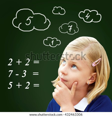 Pupil thinks standing at the blackboard. The child decides to examples in mathematics - stock photo