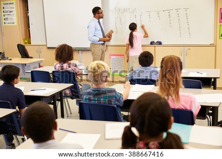 Pupil writing on the board at an elementary school class - stock photo