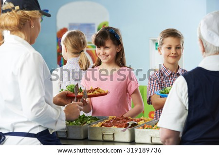 Pupils Being Served With Healthy Lunch In School Canteen - stock photo