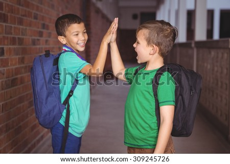 Pupils giving each other a high five on the elementary school grounds - stock photo