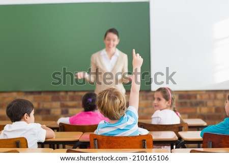 Pupils listening to their teacher at chalkboard at the elementary school - stock photo