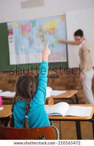 Pupils listening to their teacher at map at the elementary school - stock photo