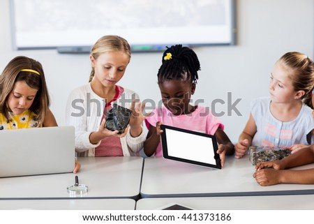 Pupils looking at rock while the others using technology in classroom - stock photo