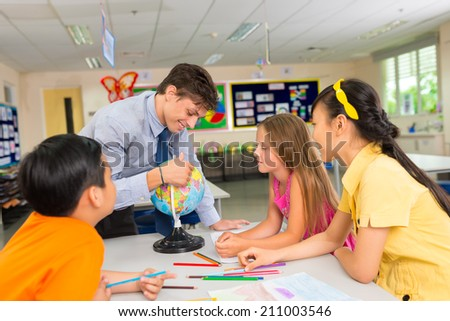 Pupils looking at the globe with their teacher during geography lesson - stock photo