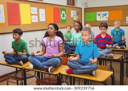 Pupils meditating on classroom desks at the elementary school - stock photo