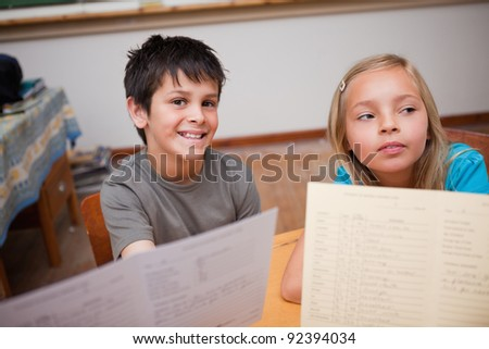 Pupils receiving their school report in a classroom - stock photo