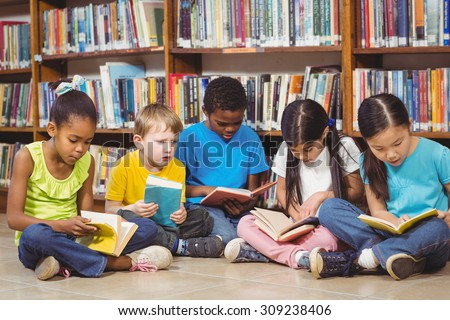 Pupils sitting on the ground and reading books in the library in school - stock photo