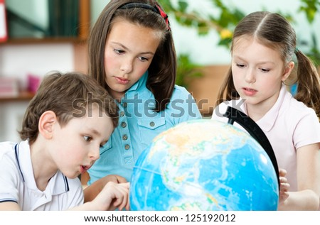 Pupils stare at the school terrestrial globe - stock photo