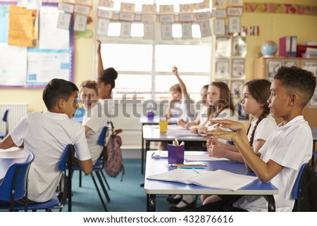 Pupils turning round in lesson at primary school, side view - stock photo