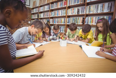 Pupils working together at desk in library at the elementary school - stock photo