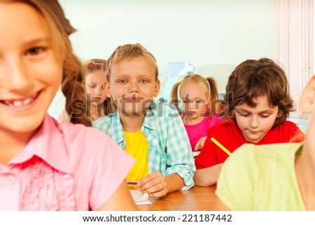 Pupils write in exercise books during lesson - stock photo