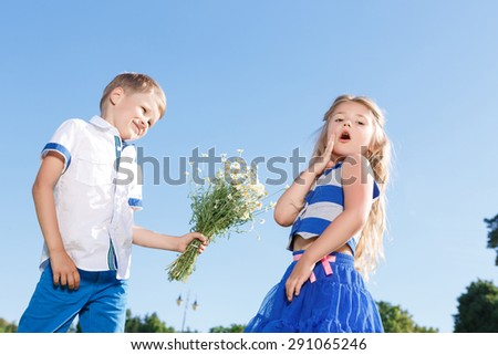 Puppy love. Nice little boy holding the bunch of flowers and presenting them to pleasant little girl showing wonder. - stock photo