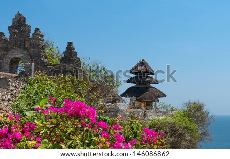 Pura Luhur Uluwatu Temple, Bali on cliffs above blue tropical sea with pink flowers on front  - stock photo