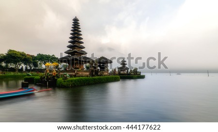Pura Ulun Danu Bratan , a Hindu temple in the evening of a rainy day of summer in Bali, Indonesia. Long exposure, image stack. Boat is seen in foreground. - stock photo