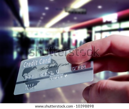 Purchasing with a credit card in a shopping mall - stock photo