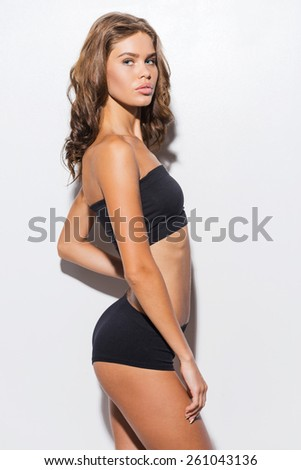 Pure beauty. Side view of attractive young brown hair woman in black lingerie posing against white background