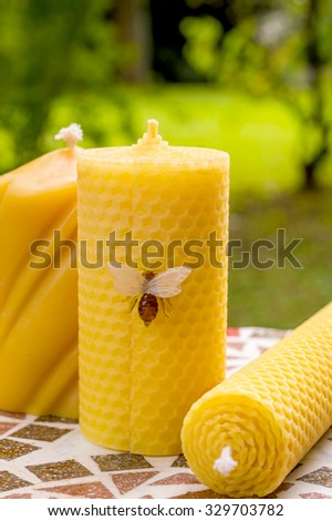 Pure beeswax natural candles on a marble table outdoor in the green nature - stock photo