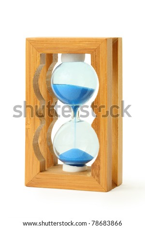 pure blue sand falls into wooden hourglass isolated on white