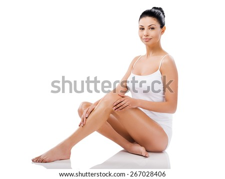 Pure perfection. Beautiful young woman looking at camera and holding hands on her legs while sitting against white background   - stock photo