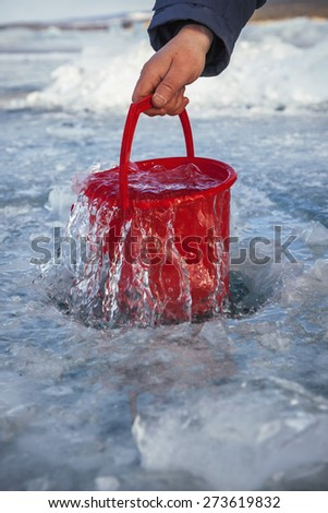 Pure water in a red bucket from the frozen Lake Baikal - stock photo