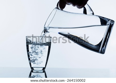 pure water is emptied into a glass of water from a jug. fresh drinking water - stock photo