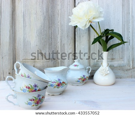 Pure white composition with single flower of peony in a porcelain vase and fine tea ware set decorated with floral pattern in a white rustic setting. Vintage decor - stock photo