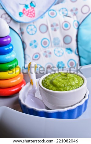 Puree of green in a small bowl stands on a childrens table for feeding - stock photo