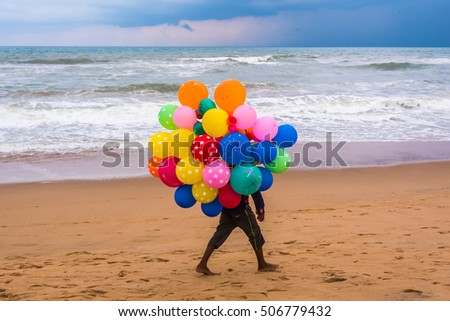 PURI - SEPTEMBER 24: A boy sells colorful balloons on the sea beach on September 24, 2016 at Puri, Odisha, India. Puri is a popular tourist destination in India.