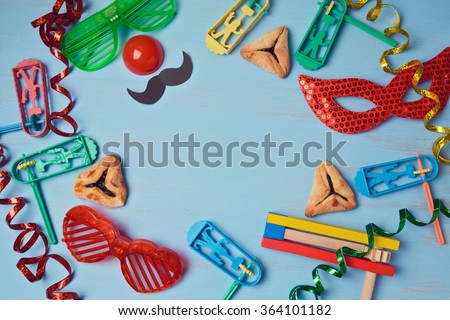 Purim background with carnival mask, party costume and  hamantaschen cookies. View from above