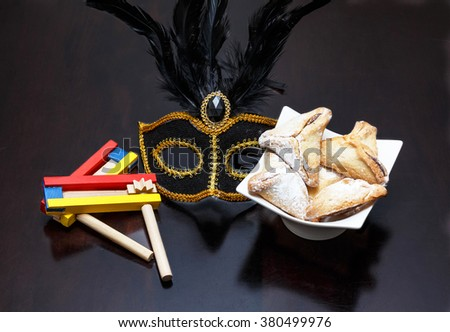 Purim holiday cookies, Ozne Haman in Hebrew Colorful noisemaker and Purim Mask - stock photo