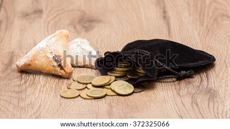"""Purim holiday cookies, """"Ozne Haman"""" in Hebrew. Haman's ears. With a bag of gold coins. Money for Purim - stock photo"""