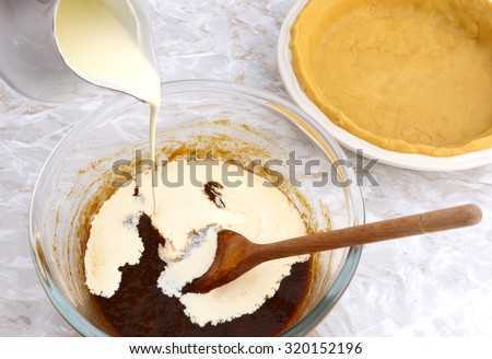 Puring double cream into pumpkin pie filling, empty shortcrust pastry case beyond - stock photo