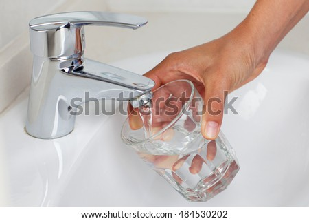 Puring in water in a glass from a tap