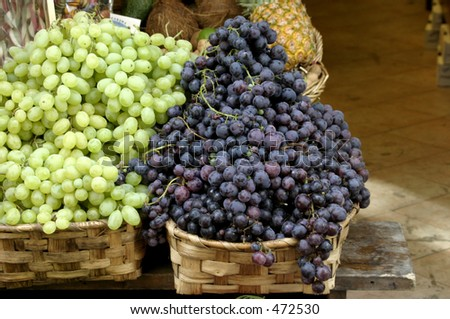 Purple and green grapes in wicker baskets - stock photo